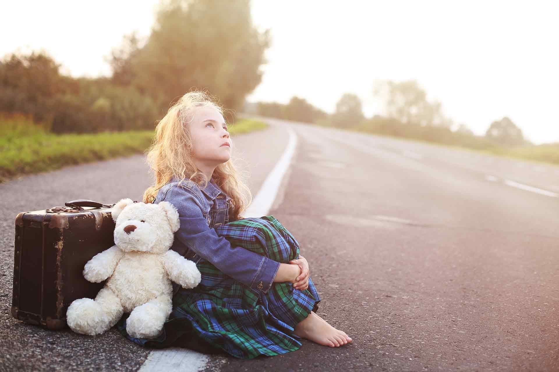Pige sidder helt alene i vejkanten med sin bamse og sin kuffert